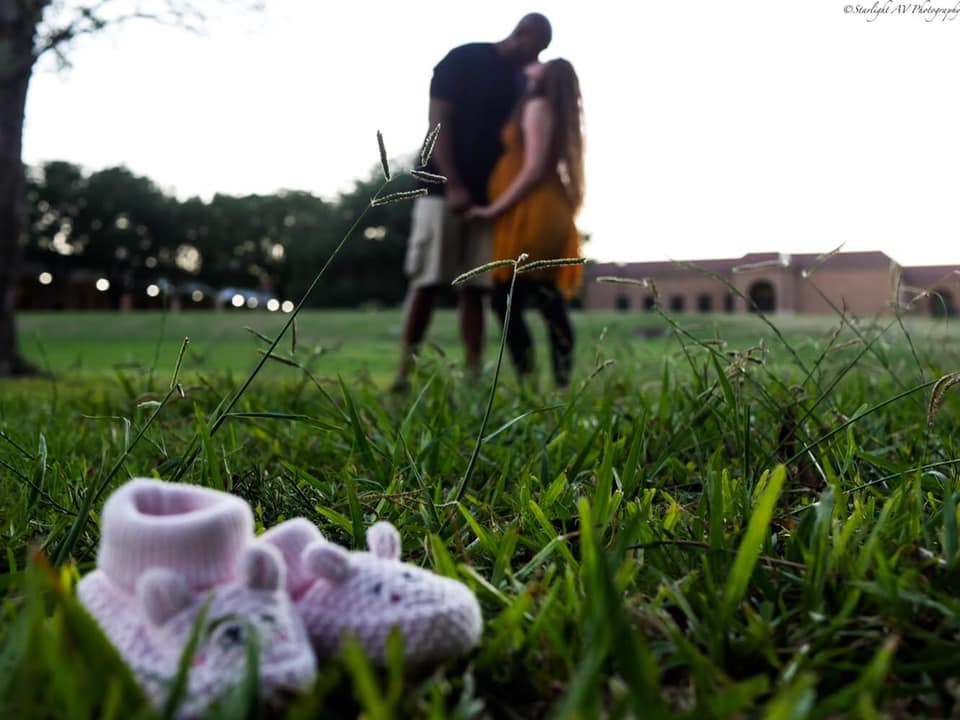 Baby slippers sitting in the grass  and a couples embrace