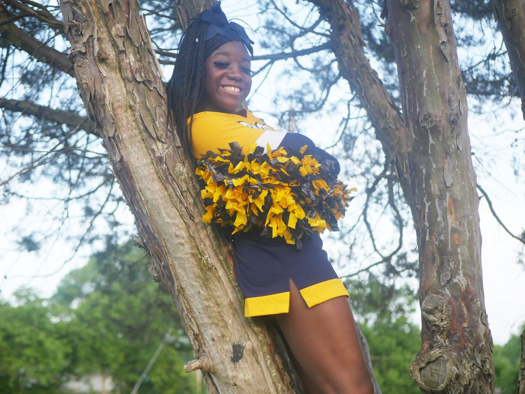 African American Teen Girl in yellow and blue cheerleader outfit standing in a tree holding pom poms