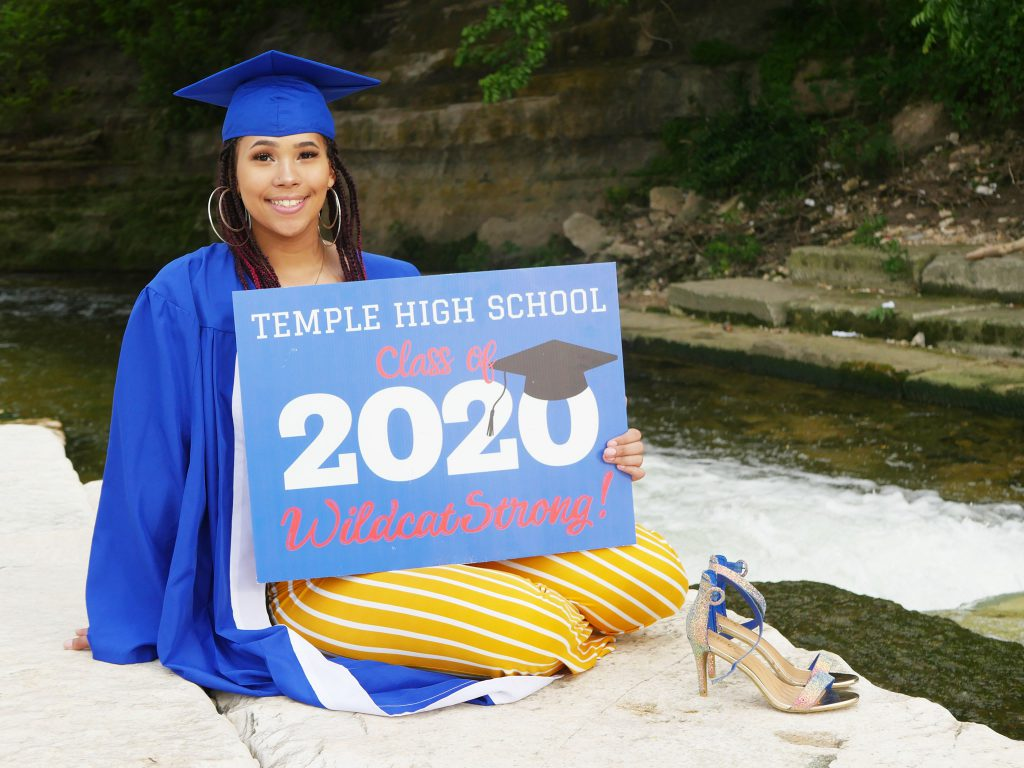 Female High School Senior Holding a 2020 sign wearing a blue cap and gown and yellow pants