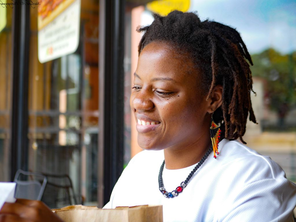 Amesha Mayo Photographer Smiling and enjoying a coffee shop with the town reflected in the window behind her